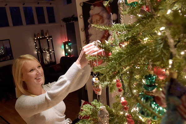 TIM JEAN/Staff photo <br /> <br /> Amber Dailey, 24, adjusts a ornament on the twelve-foot tall Christmas tree in her home in Salem, NH. Salem residents can drop of Christmas trees at the transfer station on Shannon Road.   12/31/19