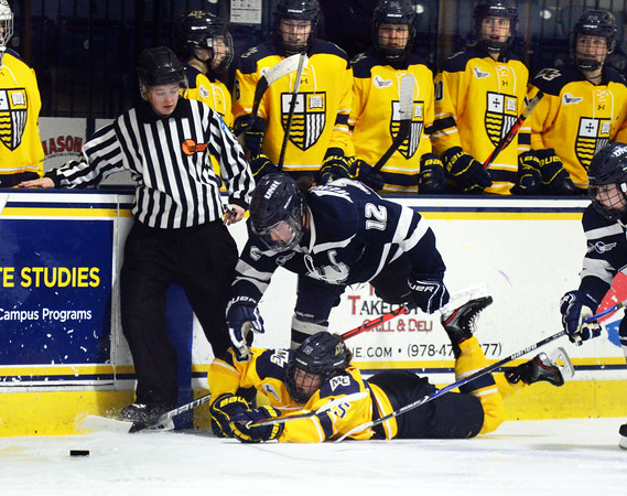 CARL RUSSO/Staff photo. UNH's Taylor Wenczkowski and Merrimack's Gabby Jones go down fighting for the puck in front of Merrimack's bench. The Merrimack College Warriors were defeated by the University of New Hampshire Wildcats in women's hockey action Friday night.12/06/2019