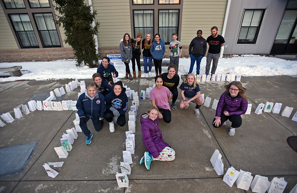 """RYAN HUTTON/ Staff photo<br /> Students and staff at the Cormier Youth Center in Andover pose with tea lights in decorated bags as part that spell out the initials for Andover Youth Services as part of the """"Light Up the Night"""" initiative."""