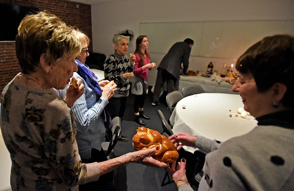 RYAN HUTTON/ Staff photo<br /> Members of Congregation Beth Israel in Andover share challah bread at the start of the Shabbat celebration on the first night of Hanukkah on Friday.