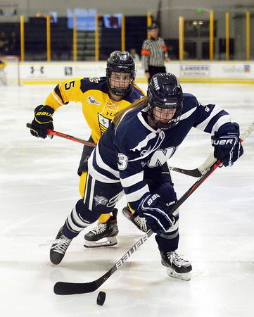 CARL RUSSO/Staff photo. Merrimack's Allison Reeb chases UNH's Annie Berry as she controls the puck. The Merrimack College Warriors were defeated by the University of New Hampshire Wildcats in women's hockey action Friday night.12/06/2019