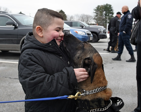 RYAN HUTTON/ Staff photo<br /> Aiden Moore, 8, gets kisses from Lawrence Police K-9 officer Magnus outside the Derry Police Department on Friday morning. Nearly a dozen police dogs and their handlers showed up to help present Aiden's family with a handicap accessible van which they will need as his Duchenne Muscular Dystrophy worsens.