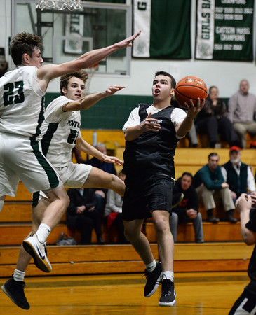 CARL RUSSO/Staff photo. North Andover's Jack Morin drive to the net against Pentucket's Jake Etter, left and Sam Stys. North Andover defeated Pentucket in boys basketball scrimmage game Tuesday afternoon. 12/10/2019