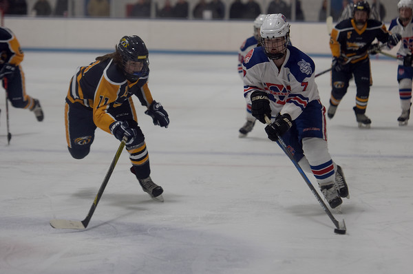 TIM JEAN/Staff photo <br /> <br /> Andover's Ashley Chiango, left, tries to defend Methuen/Tewksbury's Brenna Greene during a girls hockey game. Andover won 4-3 in overtime.     12/21/19