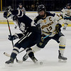 TIM JEAN/Staff photo <br /> <br /> Merrimack's Chase Gresock battles to control the puck against UNH defensemen Max Gildon during the first period of a Mens Ice Hockey game at Merrimack College.    12/7/19