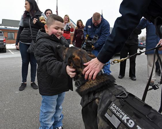 RYAN HUTTON/ Staff photo<br /> Aiden Moore, 8, pets TJ, a K-9 officer from Easton Connecticut outside the Derry Police Department on Friday morning. Nearly a dozen police dogs and their handlers showed up to help present Aiden's family with a handicap accessible van which they will need as his Duchenne Muscular Dystrophy worsens.
