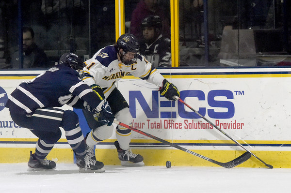 TIM JEAN/Staff photo <br /> <br /> Merrimack's Tyler Irvine looks to make a play as UNH defensemen Ryan Verrier tries to stop him during the first period of a Mens Ice Hockey game at Merrimack College.    12/7/19