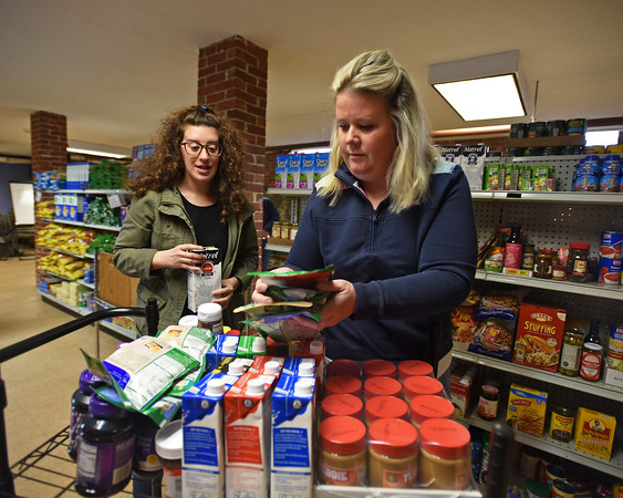 RYAN HUTTON/ Staff photo<br /> Siobhan Atwood, right, and Rachel Manning, left, stock the shelves at the Liz Murphy Open Hand Food Pantry in Haverhill on Tuesday morning.