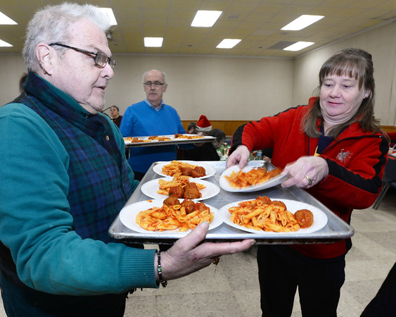 CARL RUSSO/Staff photo. STEPPING OUT: Holy Name Society member Ralph Brosco of Lawrence and Lori Ferraro of Methuen serve the dinner. <br /> <br /> The Holy Name Society of Corpus Christi Parish at Holy Rosary Church in Lawrence held its 59th. Annual Christmas Party for Exceptional Adults and Children on Sunday, December 1st. at the Parish Center. <br /> <br /> Over one hundred guest, family members and caregivers were treated to a Pasta and meatball dinner and a large Christmas cake for dessert. The highlight of the party was a visit from Santa who handed out Christmas gifts. The music was provided by The Holy Name Society's Christmas Party Band. 12/1/2019