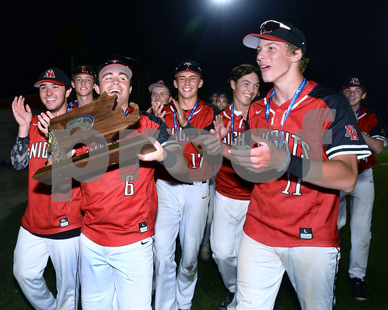 CARL RUSSO/staff photo Captain Jake McElroy carries the championship trophy as the Knights celebrate the victory. North Andover defeated St. John's Prep in the Super 8 tourney championship game Tuesday night. 6/18/2019