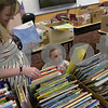 TIM JEAN/Staff photo<br /> <br /> Jaquie Keeves and her daughter Hannah, 3, of Windham, look over books from the Friends of the Library of Windham (F.L.O.W.)  annual book sale to benefit the Nesmith Library during the 36th Annual Strawberry Festival, and Windham's Nutfield 300th celebration.      6/1/19