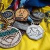 AMANDA SABGA/Staff photo<br /> <br /> Some of Lisa Doucett's many medals sit on her 2013 Boston Marathon shirt. Doucett has run 25 Boston Marathons and competed in hundred of races including running, rowing and skiing. <br /> <br /> 6/20/19