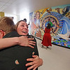"""MIKE SPRINGER/Staff photo<br /> Visual art teacher Jessica Daviso hugs junior Ethan Paulo, one of 25 student artists who created a new mural, """"The World in Andover,"""" following an unveiling event Tuesday at Andover High School. The students worked with artist-in-residence David Fichter of Cambridge to create a work celebrating Andover's diverse cultural heritage.<br /> 6/4/2019"""
