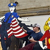 """RYAN HUTTON/ Staff photo<br /> Abigail Slevoski, 16, puts a coat of backdrop paint on Whittier Tech's parade float in preparation for Sunday's VFW Santa Parade in Haverhill. This year's theme is """"heroes""""."""