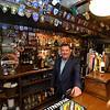 RYAN HUTTON/ Staff photo<br /> Peddler's Daughter owner Michael Conneely behind the pub's bar.