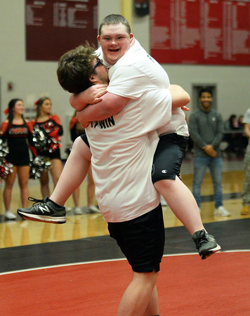 CARL RUSSO/Staff photo. David Tweedie, 2019 North Andover high school graduate jumps into the arms of his teammate, Jimmy Keith, a 2016 N.A.H.S. graduate after winning his wrestling match. <br /> <br /> The 6th. annual North Andover Wrestle 'Lympics was held Friday night at North Andover high school. High school varsity and middle school wrestlers competed against challenged wrestlers to benefit the Best Buddies program. 11/22/2019