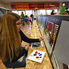 """RYAN HUTTON/ Staff photo<br /> Marelys Perez, 15, paints one of the side panels for Whittier Tech's parade float in preparation for Sunday's VFW Santa Parade in Haverhill. This year's theme is """"heroes""""."""
