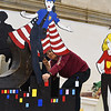 """RYAN HUTTON/ Staff photo<br /> Keily Martinez, 16, paints the Whittier Tech float to get it ready for Sunday's VFW Santa Parade in Haverhill. This year's theme is """"heroes""""."""