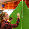 """RYAN HUTTON/ Staff photo<br /> Margot Springer, 16, paints some detail on a wooden Christmas tree for Whittier Tech's parade float in preparation for Sunday's VFW Santa Parade in Haverhill. This year's theme is """"heroes""""."""