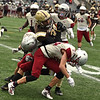 RYAN HUTTON/ Staff photo<br /> Haverhill's Jancarlos Figueroa pushes through Lowell defenders during the first quarter of Thursday's Thanksgiving game at Trinity Stadium in Haverhill. Haverhill beat Lowell 28-7.