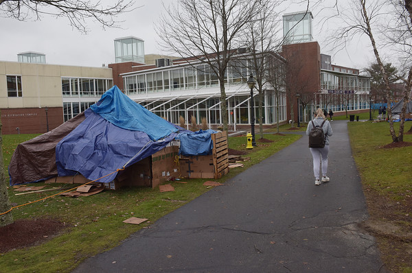 """TIM JEAN/Staff photo <br /> <br /> Students walk past one of two cardboard box """"Homeless Shelters"""" created by students near the Sakowich Center on the college campus. The students hope to bring awareness to the homeless crisis in the area and raise money for Lazarus House by sleeping out in the home. 11/20/19"""