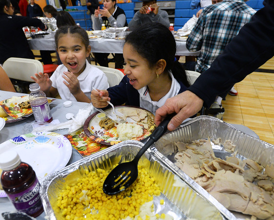 CARL RUSSO/Staff photo.  Love Gomez, left , 9 and Johanny Hilario, 8 have some fun while a volunteer serves the dinner. <br /> <br /> Over 400 youth members of the Boys & Girls Club of Lawrence enjoyed a traditional Thanksgiving dinner with all the trimmings  Tuesday night. The dinner was donated and prepared by members of the Exchange Club of Lawrence and served by volunteers. The Exchange Club also donated a check for $2,000 to the Boys & Girls Club before the start of dinner. <br /> <br /> In addition, Executive Director Markus Fischer presented the club's 2020 Youth of the Year award to Joel Javier of Lawrence. He is a senior at the Greater Lawrence Technical high school majoring in Information Technology. <br /> <br /> Established in 1947, Youth of the Year is the Boys & Girls Club of America's premier recognition program for club members 14-18 years old who compete at the local, state, regional and national levels for college scholarships. The National Youth of the Year is installed by the President of the United States. 11/26/2019