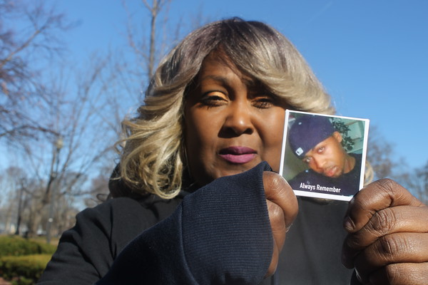 """MIKE LABELLA/Staff photo<br /> <br /> Denise Murray holds a photo of her son, Timothy Walker, who in 2010 was killed in an act of violence in Lawrence. Murray took part in Saturday's """"Lawrence Against Violence"""" walk at the Campagnone Common."""