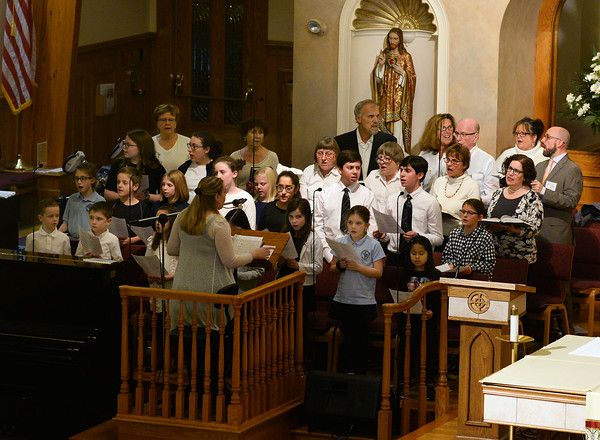 CARL RUSSO/staff photo. St. Michael's choir director, Brinn Kingsley-Marquez conducts the children and adult choir during the mass. Cardinal Sean P. O'Malley, OFM Cap. celebrated mass Tuesday night at St. Michael's Parish in honor of their 150th anniversary. 11/19/2019