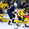 CARL RUSSO/Staff photo. Merrimack's Regan Kimens, 16 and Tyler Irvine fight for the puck with Penn State's Kevin Wall. Merrimack College was defeated by Penn State in men's hockey Friday night. 11/29/2019