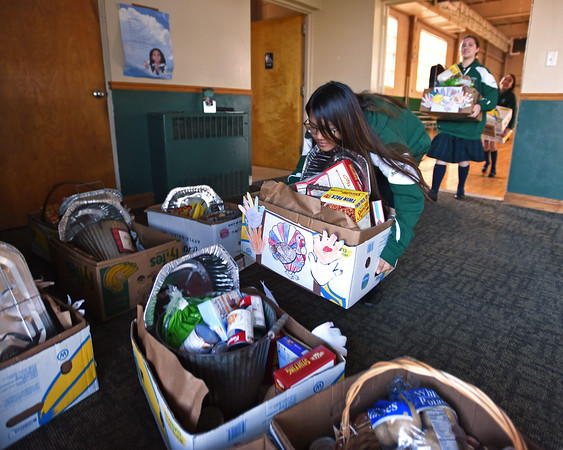 RYAN HUTTON/ Staff photo<br /> Jhona Bel Lazarte, 14, piles up donation boxes full of Thanksgiving groceries at the St. Joseph Regional Catholic School on Monday.
