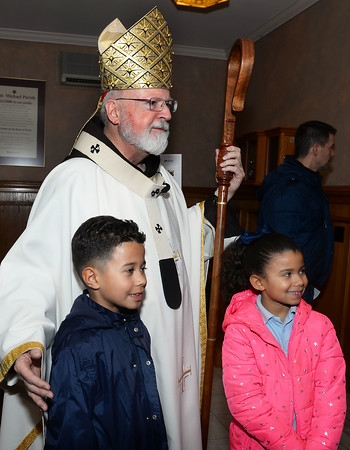 CARL RUSSO/staff photo. St. Michael's students Emmanuel Surun, a 3rd. grader and his sister, Diana, 2nd. grader meet Cardinal Sean P. O'Malley, OFM Cap. after mass. They live in Methuen. <br /> <br /> Cardinal Sean P. O'Malley, OFM Cap. celebrated mass Tuesday night at St. Michael's Parish in honor of their 150th anniversary. 11/19/2019