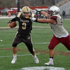 RYAN HUTTON/ Staff photo<br /> Haverhill quarterback Brady Skafas pushes off a Lowell defender during the fourth quarter of Thursday's Thanksgiving game at Trinity Stadium in Haverhill. Haverhill beat Lowell 28-7.