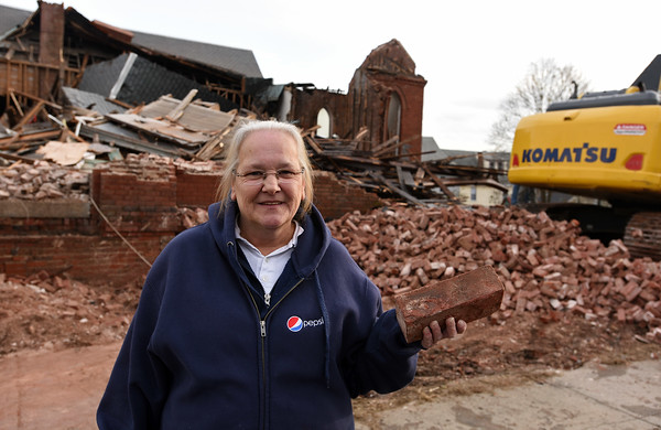 RYAN HUTTON/ Staff photo<br /> Joan Graciale holds up one of the bricks she retrieved from the demolition site at the old St. George church on Washington Street in Haverhill on Thursday. Graciale said she wanted a memento from the 127-year0old building because she got married at the church in 1980 and all her children were baptized there.