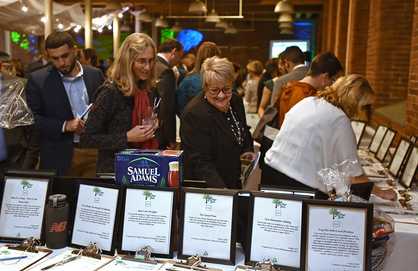 RYAN HUTTON/ Staff photo<br /> Jeanne Osborn, right, looks over some of the auction items up for bod at the GLOW Gala at Everett Mill in Lawrence on Thursday night marking the 20th anniversary of Groundwork Lawrence.