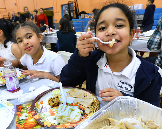CARL RUSSO/Staff photo.  Love Gomez, left , 9 and Johanny Hilario, 8 enjoy their dinner.  <br /> <br /> Over 400 youth members of the Boys & Girls Club of Lawrence enjoyed a traditional Thanksgiving dinner with all the trimmings  Tuesday night. The dinner was donated and prepared by members of the Exchange Club of Lawrence and served by volunteers. The Exchange Club also donated a check for $2,000 to the Boys & Girls Club before the start of dinner. <br /> <br /> In addition, Executive Director Markus Fischer presented the club's 2020 Youth of the Year award to Joel Javier of Lawrence. He is a senior at the Greater Lawrence Technical high school majoring in Information Technology. <br /> <br /> Established in 1947, Youth of the Year is the Boys & Girls Club of America's premier recognition program for club members 14-18 years old who compete at the local, state, regional and national levels for college scholarships. The National Youth of the Year is installed by the President of the United States. 11/26/2019