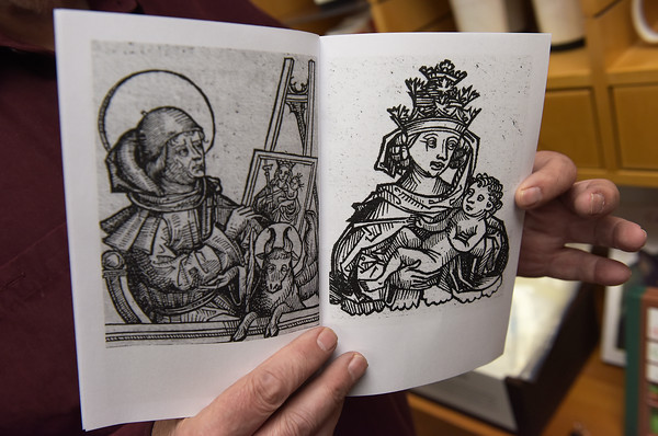 TIM JEAN/Staff photo <br /> <br /> Frank Romano holds up pages in a Nuremberg Chronicle children's coloring book on sale in the gift shop in Museum of Printing in Haverhill. The museum has several pages from the Nuremberg Chronicle on display.      11/14/19