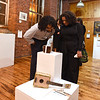 RYAN HUTTON/ Staff photo<br /> Mekhi Mendoza, left, and Celeste Cruz, right, check out some of the art work on display at the GLOW Gala at Everett Mill in Lawrence on Thursday night marking the 20th anniversary of Groundwork Lawrence.