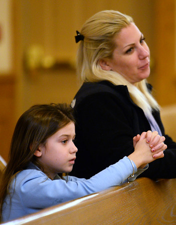 CARL RUSSO/staff photo. Kate Machowski of North Andover and her daughter, Maria Jimenez, a 3rd. grader at St. Michael's School attend the mass. <br /> <br /> Cardinal Sean P. O'Malley, OFM Cap. celebrated mass Tuesday night at St. Michael's Parish in honor of their 150th anniversary. 11/19/2019
