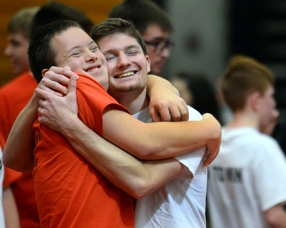 CARL RUSSO/Staff photo. Jack Perry, right, NAHS graduate and a junior at UMass Amherst hugs his brother Zane Perry, a junior at NAHS after wrestling each other. Jack started the North Andover Wrestle 'Lympics six years ago.  <br /> <br /> The 6th. annual North Andover Wrestle 'Lympics was held Friday night at North Andover high school. High school varsity and middle school wrestlers competed against challenged wrestlers to benefit the Best Buddies program. 11/22/2019