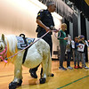 RYAN HUTTON/ Staff photo<br /> Peaches the mini horse stands on stage at High Plain Elementary School during an anti-bullying assembly on Friday with Andover Police Sgt. Steven Gerroir and students, from left, fifth grader Adelaide Buzay, second grader Akshanan Thiraviyarajah, first grader Maxwell Njenga, and fifth grader Rayna Cozzaglio.