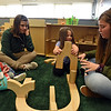 RYAN HUTTON/ Staff photo<br /> Laura Gould, 4, center right, holds up a building block to Whittier Tech student Brooke Gates, 17, while Liam Fay, 3, and Madison Herries, 17, look on at Whittier's new early childhood education center established through a partnership with the YMCA.