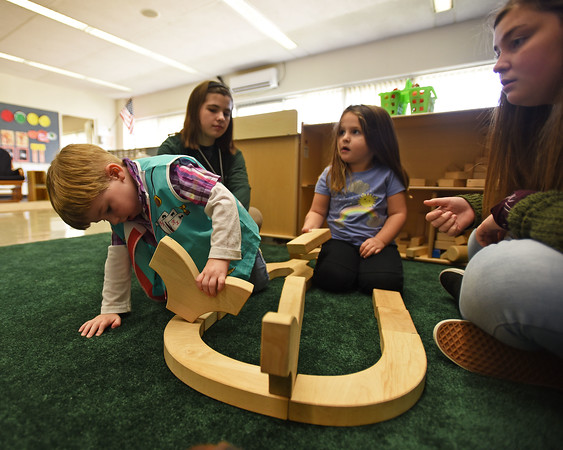 RYAN HUTTON/ Staff photo<br /> Liam Fay, 3, and Laura Gould, 4, build build a road out of blocks with Whittier Tech students Madison Herries, 17, left, and Brooke Gates, 17, right, at Whittier's new early childhood education center established through a partnership with the YMCA.