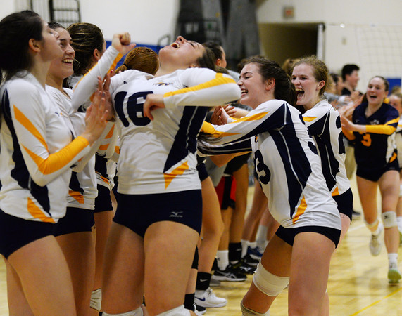 CARL RUSSO/Staff photo Andover's from left, Angelina Archambeault, 16, Marissa Kobelski and Hannah Goff celebrate with their teammates. Andover defeated Methuen in the 5th. game of volleyball action at Andover high. 10/7/2019