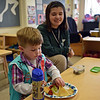 RYAN HUTTON/ Staff photo<br /> Whittier Tech student Madison Herries, 17, looks on as Liam Fay, 3, eats lunch at Whittier's new early childhood education center established through a partnership with the YMCA.
