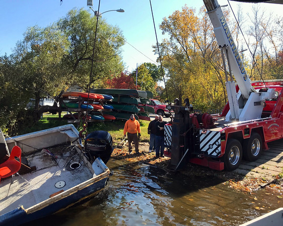 PHOTO COURTESY ROCKY MORRISON<br /> A team from the Clean River Project uses a crane and an inflatable pontoon to raise a Lawrence Community Boating Program boat from the bottom of the Merrimack River on Monday morning after it sank during last week's nor'easter.