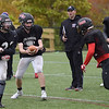 TIM JEAN/Staff photo<br /> <br /> North Andover football coach John Dubzinski, center, watches his quarterback Peter Radulsk, hand the ball off as they work on offensive plays during practice Tuesday.   10/22/19