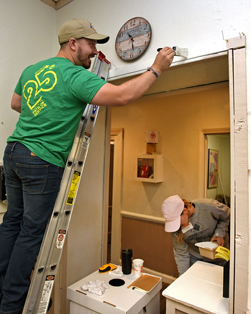 "RYAN HUTTON/ Staff photo<br /> Timberland employee Kevin Pagdon paints door trim while coworker Emily Miller paints a shelving unit at the Bread & Roses soup kitchen on Newbury Street in Lawrence during the company's ""Serv-a-Palooza"" community service event on Wednesday."