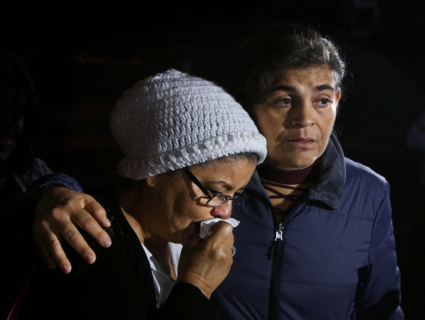 MIKE SPRINGER/Staff photo<br /> Antonia Puello Rodriguez, left, is comforted by her sister Ana Maria Puello Rodriguez while the two talked about their brother, the late Jose Puello Rodriguez, during a press conference Tuesday evening outside the Lawrence Senior Center. Jose, 60, died last weekend after being in a coma since a Sept. 16 altercation at the center.<br /> 10/15/2019
