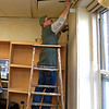 "RYAN HUTTON/ Staff photo<br /> Timberland employee Jay Codico paints wall trim at the Bread & Roses soup kitchen on Newbury Street in Lawrence during the company's ""Serv-a-Palooza"" community service event on Wednesday."