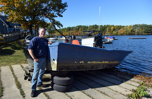 """RYAN HUTTON/ Staff photo<br /> Richard """"Rocky"""" Morrison, head of the Clean River Project, stands with the Lawrence Community Boating Program boat his team helped find and raise from the bottom of the Merrimack River on Monday morning after it sank during last week's nor'easter."""